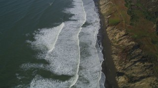 DFKSF15_047 - 5K stock footage aerial video of a reverse view of ocean waves rolling toward a beach and coastal cliffs, Lakeshore District, San Francisco, California