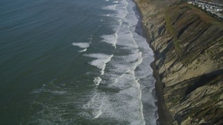 DFKSF15_048 - 5K stock footage aerial video of flying away from ocean waves rolling toward coastal cliffs, Daly City, California