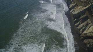 DFKSF15_049 - 5K stock footage aerial video of a reverse view of ocean waves rolling into coastal cliffs, Daly City, California