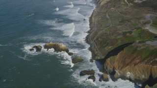 DFKSF15_050 - 5K stock footage aerial video fly away from waves rolling into coastal cliffs and rock formations, Daly City, California