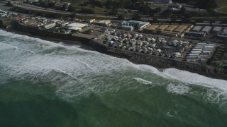 DFKSF15_051 - 5K stock footage aerial video of flying by oceanfront homes as waves roll in, Pacifica, California