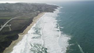 DFKSF15_062 - 5K stock footage aerial video of flying over Montara State Beach, tilt revealing coastal neighborhoods, Montara, California