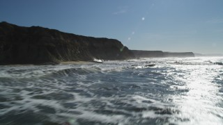 DFKSF15_081 - 5K stock footage aerial video of flying low over the ocean near cliffs, Half Moon Bay, California