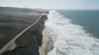 DFKSF15_090 - 5K stock footage aerial video of tilting from the coastal beach revealing Highway 1, San Gregorio, California