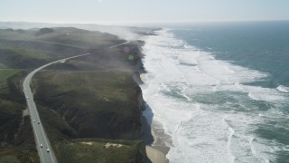 DFKSF15_093 - 5K stock footage aerial video tilt from Highway 1 and fly over coastal cliffs, Pescadero, California