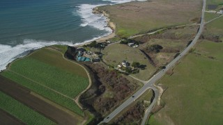 DFKSF15_112 - 5K stock footage aerial video of a reverse view of Highway 1 on the coast, revealing crop fields, Davenport, California