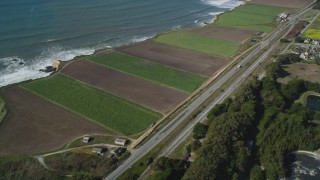 DFKSF15_113 - 5K stock footage aerial video of flying away from Highway 1 along the coast and crop fields, Davenport, California