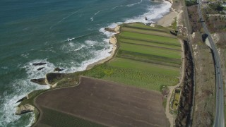 DFKSF15_114 - 5K stock footage aerial video of a reverse view of Highway 1, train tracks and crop fields, Davenport, California