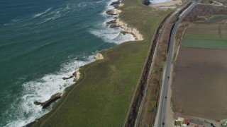 DFKSF15_115 - 5K stock footage aerial video of a reverse view of Highway 1 coastal road and train tracks, Davenport, California