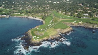 DFKSF16_033 - 5K stock footage aerial video tilt from the ocean to reveal a golf course on the coast in Pebble Beach, California