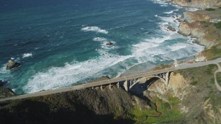DFKSF16_069 - 5K stock footage aerial video of flying away from Rocky Creek Bridge above coastal cliffs, Carmel, California