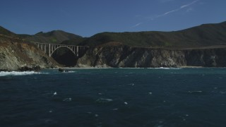 DFKSF16_072 - 5K stock footage aerial video of flying by coastal rock formation, revealing Bixby Creek Bridge, Big Sur, California