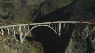 DFKSF16_076 - 5K stock footage aerial video of flying away from Bixby Creek Bridge above coastal cliffs, Big Sur, California