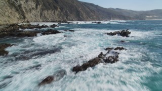 DFKSF16_078 - 5K stock footage aerial video fly low, tilt up to reveal rock formations and coastal cliffs, Big Sur, California