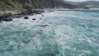 DFKSF16_080 - Aerial stock footage of 5K aerial \video of flying over the ocean, tilt up to reveal coastal cliffs, Big Sur, California