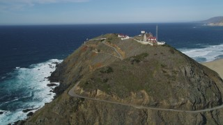 DFKSF16_091 - 5K stock footage aerial video of flying around back of Point Sur Light Station, above the coastline, Big Sur, California