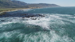 DFKSF16_095 - 5K stock footage aerial video tilt from ocean, reveal seagulls flying over rocks along coast, Big Sur, California