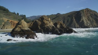 DFKSF16_105 - 5K stock footage aerial video of passing a rock formation near coastal cliffs, Big Sur, California