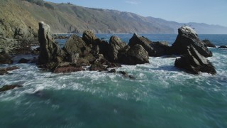 DFKSF16_106 - 5K stock footage aerial video tilt from ocean to reveal rock formation near coastal cliffs, Big Sur, California