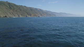 DFKSF16_107 - 5K stock footage aerial video of tilting up from the ocean to reveal coastal cliffs, Big Sur, California