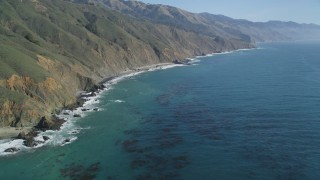 DFKSF16_108 - 5K stock footage aerial video of flying over the ocean, tilt up to reveal coastal cliffs, Big Sur, California