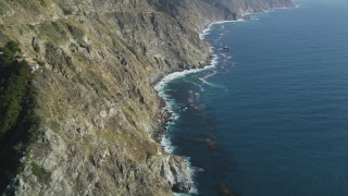 DFKSF16_113 - 5K stock footage aerial video of flying over rocky beach, tilting up along coastal cliffs, Big Sur, California