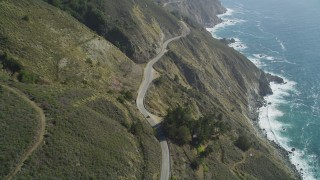 DFKSF16_116 - 5K stock footage aerial video of flying over the Highway 1 road atop coastal cliffs, tilt to cars, Big Sur, California
