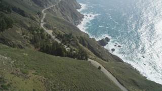 DFKSF16_117 - 5K stock footage aerial video fly over Highway 1 winding atop cliffs, tilt to reveal ocean views, Big Sur, California