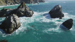 DFKSF16_122 - 5K stock footage aerial video of flying between large rock formations, tilt revealing coastal cliffs, Big Sur, California