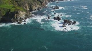 DFKSF16_124 - 5K stock footage aerial video of tilting from the ocean to reveal coastal cliffs, Big Sur, California