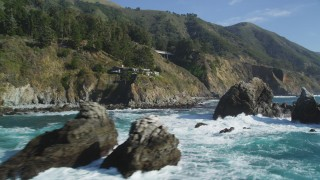 DFKSF16_125 - 5K stock footage aerial video tilt from the ocean to reveal rock formations, home atop coastal cliff, Big Sur, California
