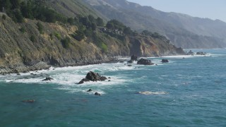 DFKSF16_127 - 5K stock footage aerial video of flying low by steep coastal cliffs and rock formations, Big Sur, California