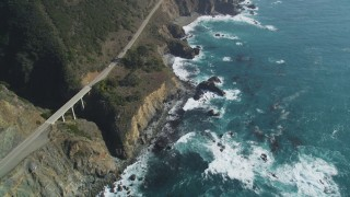 DFKSF16_130 - 5K stock footage aerial video of flying by a small bridge and Highway 1 atop coastal cliffs, Big Sur, California