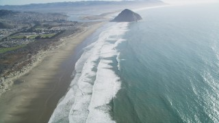 DFKSF16_153 - 5K stock footage aerial video of tilting from Morrow Strand Beach revealing Morro Rock, Morro Bay, California