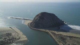 DFKSF16_156 - 5K stock footage aerial video of flying by Morro Rock beside the ocean, Morro Bay, California