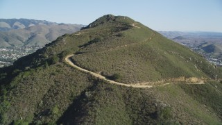 DFKSF16_159 - 5K stock footage aerial video tilt up slope of a mountain with dirt roads in San Luis Obispo, California