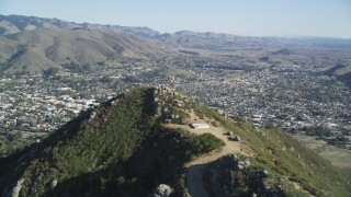DFKSF16_160 - 5K stock footage aerial video of flying over a mountain with dirt roads, revealing San Luis Obispo, California