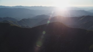 DFKSF17_019 - 5K stock footage aerial video tilt from shadowy slopes to hazy mountains, San Luis Obispo County, California