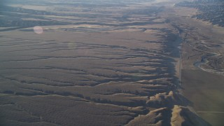 DFKSF17_024 - 5K stock footage aerial video of flying by cracks in the desert and Highway 166, Cuyama Valley, California