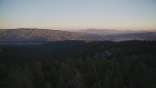 DFKSF17_053 - Aerial stock footage of 5K aerial of flying low over trees toward mountains, Los Padres National Forest, California, twilight