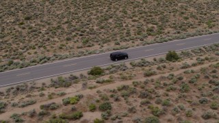 DX0001_000127 - 5.7K stock footage aerial video of tracking a black SUV on a desert road in Carson City, Nevada
