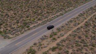 DX0001_000128 - 5.7K stock footage aerial video approach a black SUV parked on a desert road in Carson City, Nevada