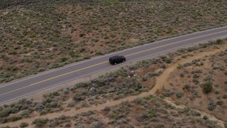 DX0001_000129 - 5.7K stock footage aerial video track a black SUV driving on a desert road in Carson City, Nevada