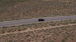 DX0001_000130 - 5.7K stock footage aerial video track a black SUV as it drives on a desert road in Carson City, Nevada
