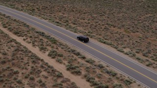 DX0001_000132 - 5.7K stock footage aerial video track a black SUV as travels on a desert road in Carson City, Nevada