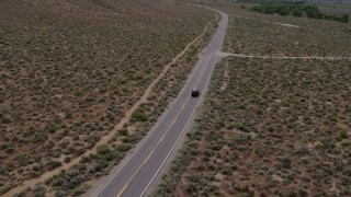 DX0001_000133 - 5.7K stock footage aerial video of a black SUV traveling on a desert road in Carson City, Nevada