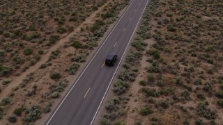 DX0001_000134 - 5.7K stock footage aerial video of a black SUV pulling onto a desert road in Carson City, Nevada