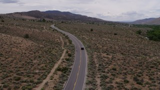 DX0001_000135 - 5.7K stock footage aerial video of a black SUV cruising on a desert road in Carson City, Nevada