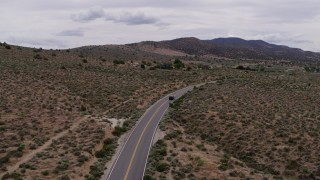 DX0001_000136 - 5.7K stock footage aerial video of following a black SUV cruising on a desert road in Carson City, Nevada