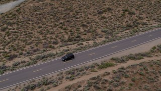 DX0001_000137 - 5.7K stock footage aerial video of a black SUV driving on a desert road in Carson City, Nevada